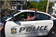 Passaic Police Officer Waving a Small American Flag out of His Cruiser Window