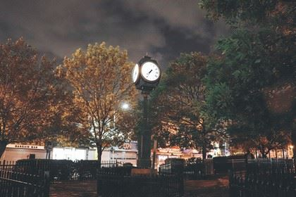 A Park Clock Lit up in  the Center of a Plaza